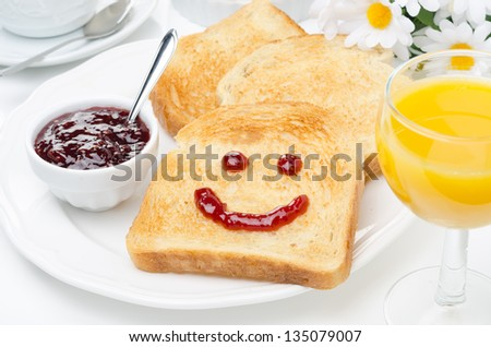 Toast with a smile of jam, coffee, orange juice and fresh oranges for breakfast, horizontal closeup