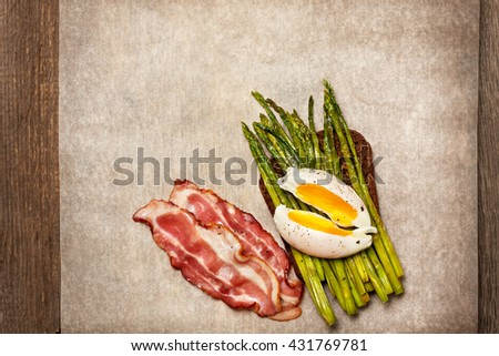toast with baked asparagus, boiled egg, bacon on paper (top view) - stock photo