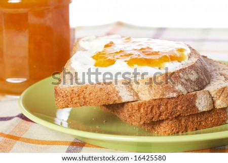 Toast with butter and peach jam glass jar in the green plate with soft shadow on square mat background. Shallow depth of field