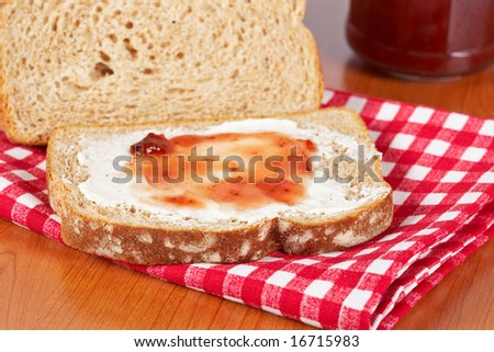 Toast with butter and strawberry jam glass jar on square mat background. Shallow depth of field