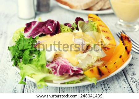 Toast with egg Benedict and greens on plate on wooden table - stock photo