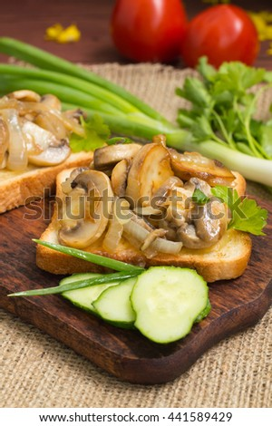 Toast with fried mushrooms and vegetables on the background color. Close-up