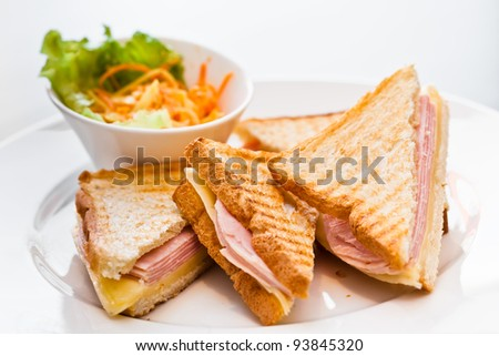 Toast with ham and cheese on the white plate with the bowl of grated carrots and lettuce - stock photo