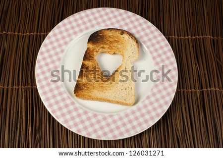 Toast with heart-shaped set in white plate