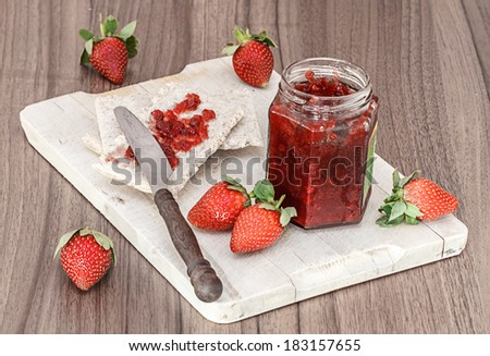 toast with jam, strawberries and knife on wood desk - stock photo