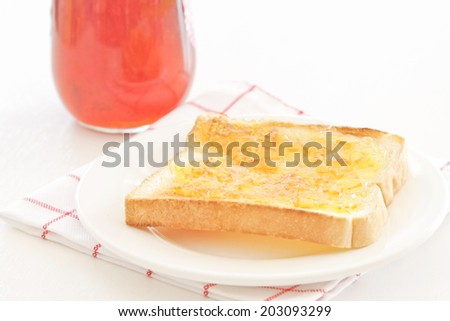 Toast with orange jam on a white plate