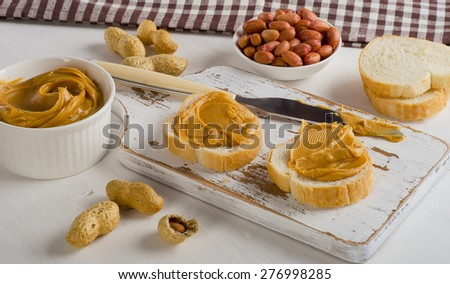 Toast with Peanut butter  and peanuts on  white wooden board.   - stock photo