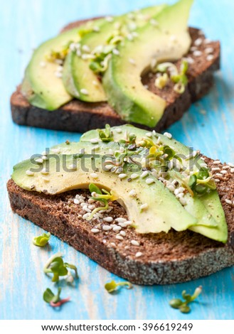 toast with slices of avocado and spices, sesame seeds,seedlings  on a wooden background - stock photo