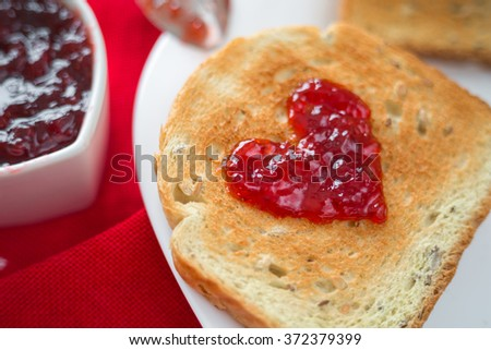 Toast with strawberry jam in a heart shape. Valentine's Day