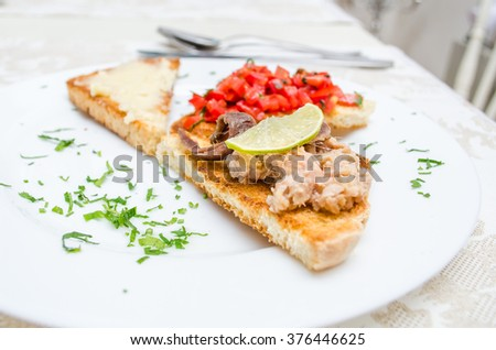 Toast with tomato, fish and cheese
