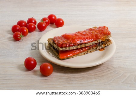 toast with tomato ketchup and red pepper on a beige plate on a light table