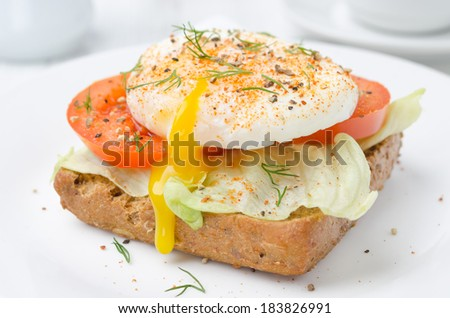 toast with tomato, lettuce and poached egg on a white plate for breakfast - stock photo