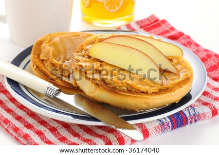 Toasted bagel with peanut butter and apple slices. - stock photo
