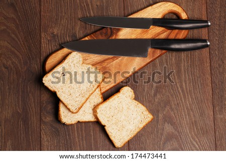 Toasted bread and knives on a cutting board - stock photo