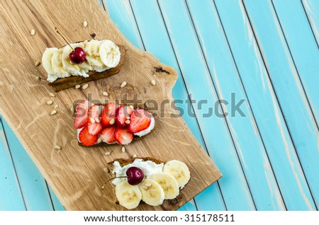 Toasted bread bruschetta with fresh creamy cheese ricotta, strawberries and cherries, bananas and cedar nuts on chopping board over rustic styled wooden turquoise table. Rustic background top view.