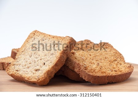 Toasted bread on a kitchen wooden board. - stock photo