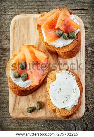 toasted bread slices with cream cheese and smoked salmon on wooden cutting board, top view - stock photo
