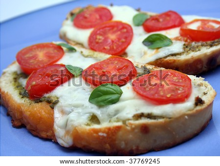 Toasted Bread Slices with pesto, tomato, basil and melted cheese - stock photo