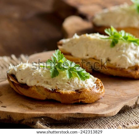 Toasted bread with a salted codfish mousse on wooden cutting board - stock photo