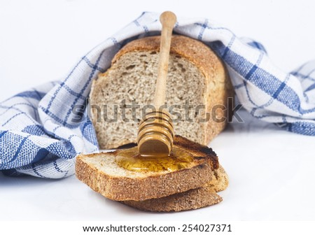 Toasted bread with honey and honey dipper isolated on white studio background. - stock photo