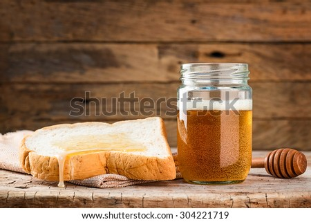 toasted bread with honey on wood table still life - stock photo