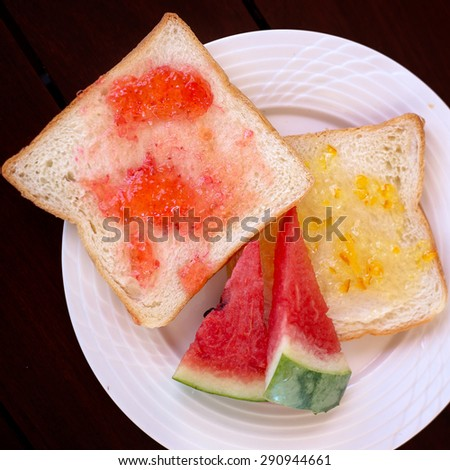 Toasted bread with strawberry jam and orange jam with sliced water melon prepared for breakfast from top view - stock photo