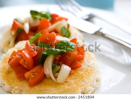 Toasted bread with sweet plum tomato salad with onions and basil with drizzling of olive oil, serve on white plate. - stock photo