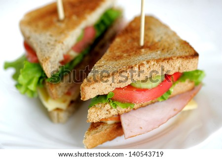 Toasted club sandwiches, tomato, meat and cheese. - stock photo