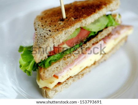 Toasted club sandwiches, tomato, meat and cheese.