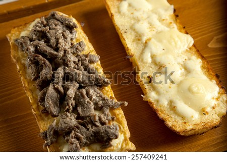 Toasted open faced beef steak sandwich with melted mozzarella cheese - stock photo