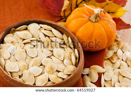 Toasted pumpkin seeds in a wooden bowl with scattered seeds and small pumpkin