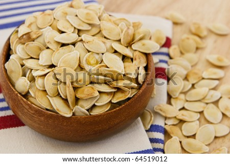 Toasted pumpkin seeds scattered against a table and striped towel with shallow depth of field - stock photo