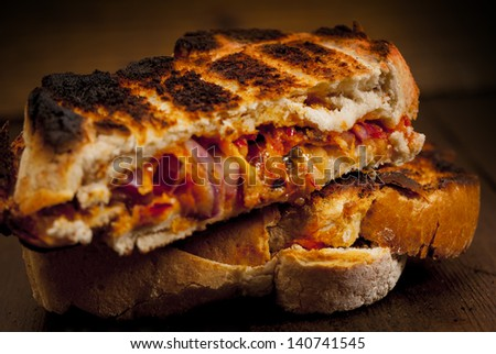 Toasted  sandwich. Toasted cheese, tomato and onion sandwich done on the BBQ. - stock photo