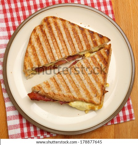 Toasted sandwich with bacon, egg and cheese. - stock photo