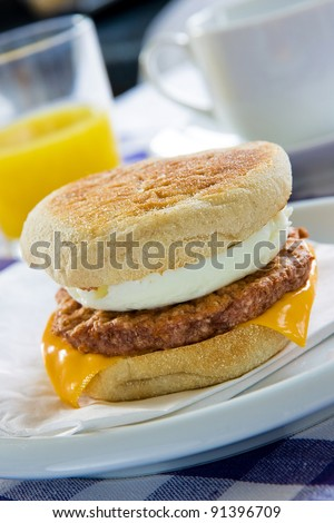 Toasted sausage and egg muffin on a breakfast table - stock photo