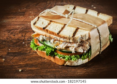 Toasted shredded chicken breast and salad sandwich served on a rustic wooden table wrapped in a brown paper wrapper tied with string with vignetting and copyspace - stock photo