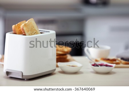 Toaster with dishes and sandwiches on a light kitchen table - stock photo