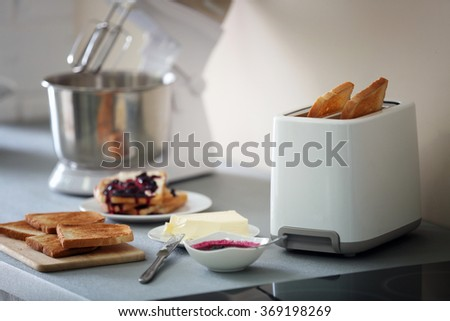 Toaster with mixer and sandwiches on a light kitchen table - stock photo