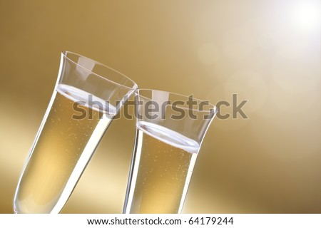 Toasting a celebration with champagne glasses on gold background for copy - stock photo