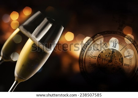 Toasting with two champagne glasses against fireworks and holiday lights - stock photo