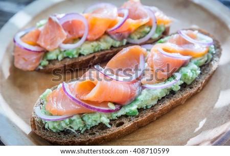 Toasts with avocado and smoked salmon - stock photo