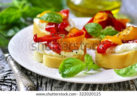 Toasts with brynza and grilled sweet pepper on a white plate.