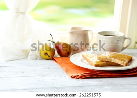 Toasts with honey on plate with cup of tea on bright background - stock photo