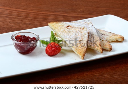 Toasts with powdered sugar and strawberry jam
