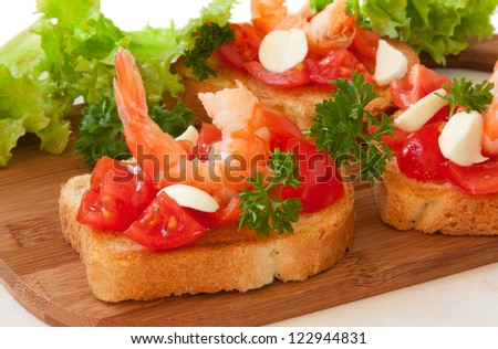 toasts with tomatoes and shrimp on a cutting board