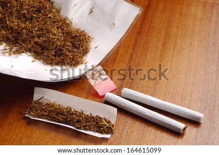 Tobacco and hand rolled cigarettes on table - stock photo