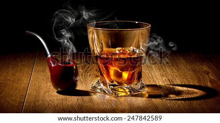 Tobacco pipe and whiskey on a wooden table - stock photo