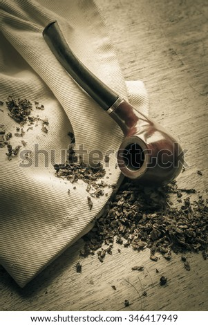 Tobacco pipe on rustic warn wood surface with spilled natural tobacco - stock photo