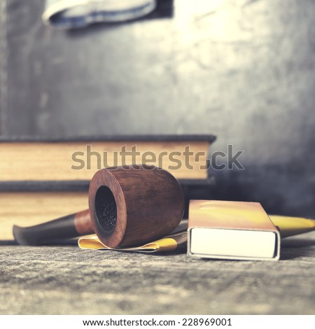 Tobacco pipe, tobacco and matches on on table. Filtered image with vintage effect  - stock photo