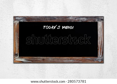 Today's menu on vintage chalk board over white cement wall background - stock photo
